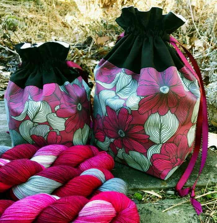 A pink and white floral bag with pink and white yarn.