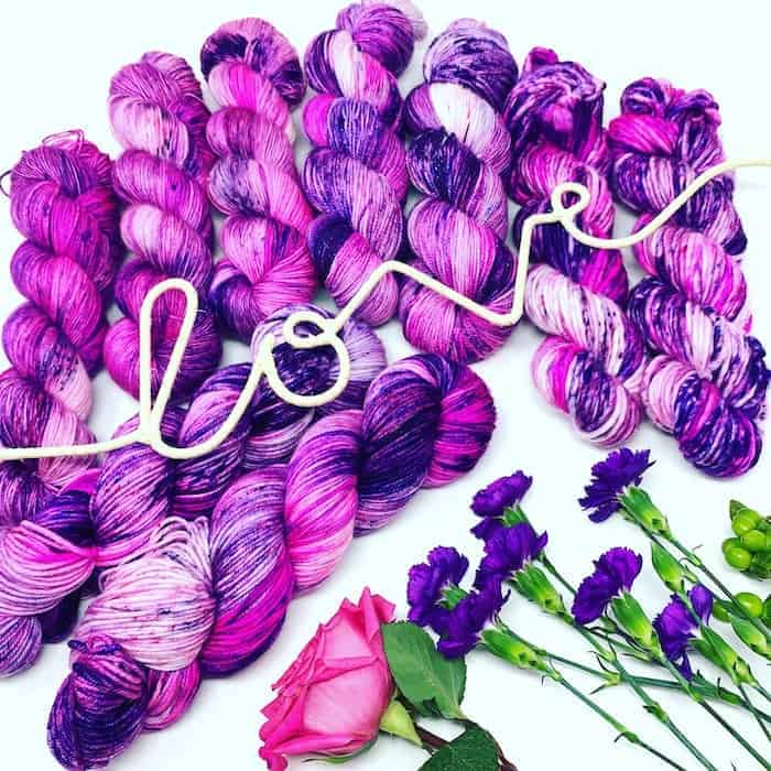 Purple and pink yarn with the word love spelled in rope.