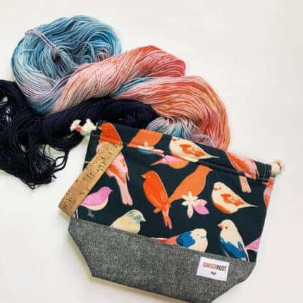 A bag with birds and red and blue yarn.