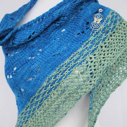 A blue and green lacy shawl with a silver shawl pin.