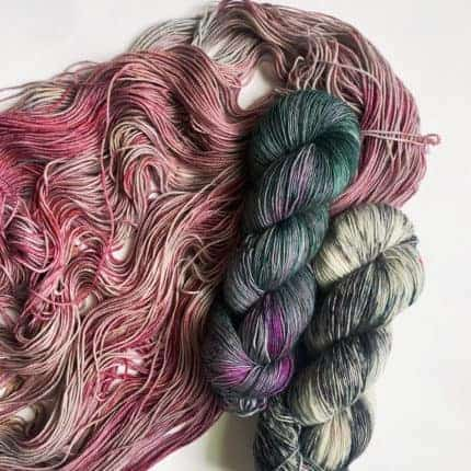 Skeins of yarn in pink, purple, gray and teal.