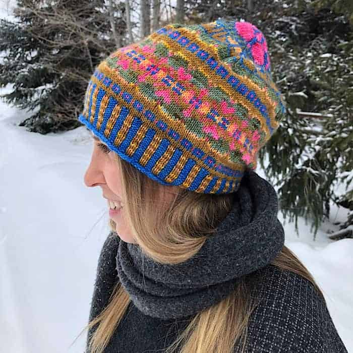 A bright colorwork hat with pink, blue and gold.