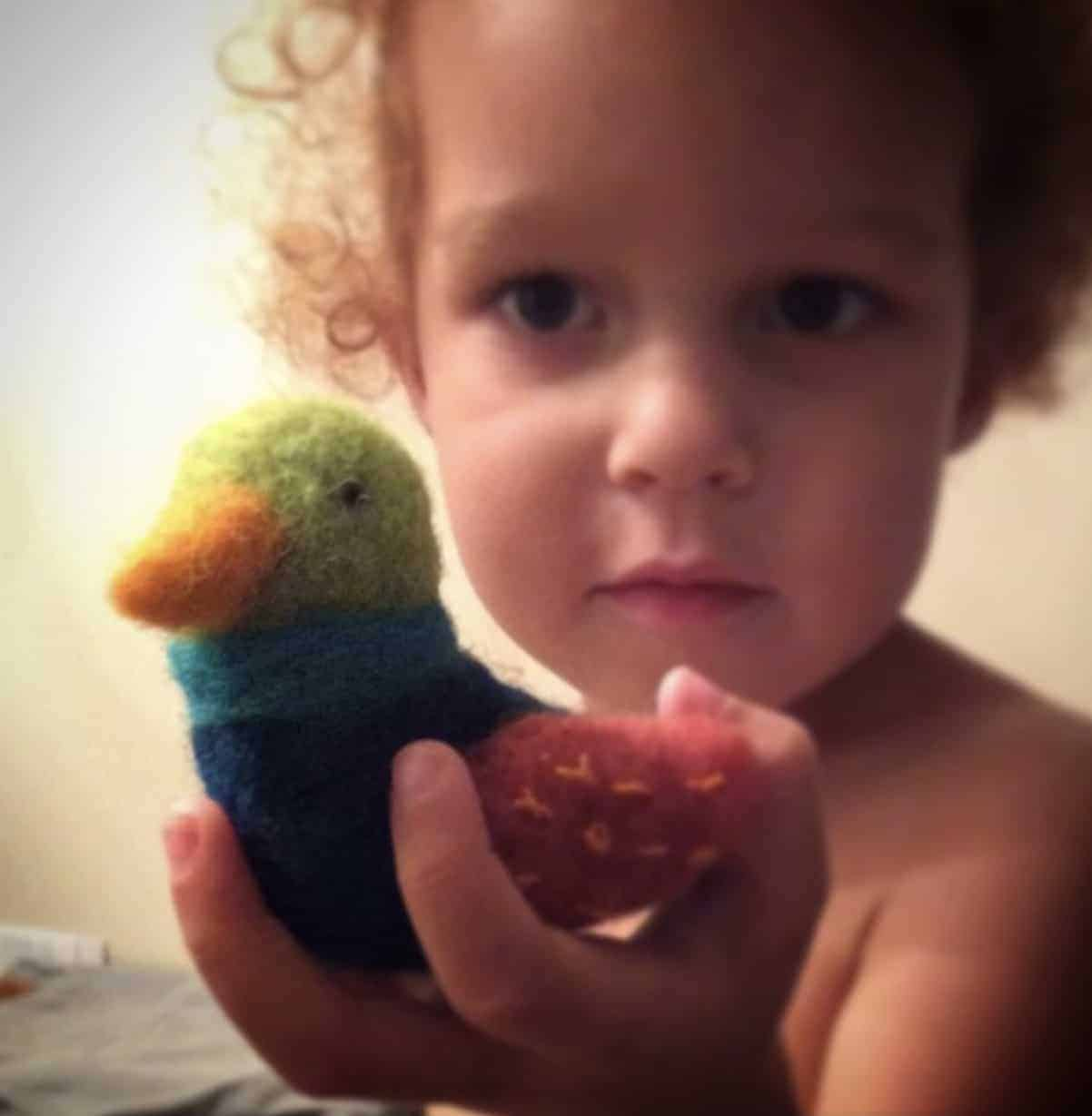 A girl holds a felted duck in green, blue and red.