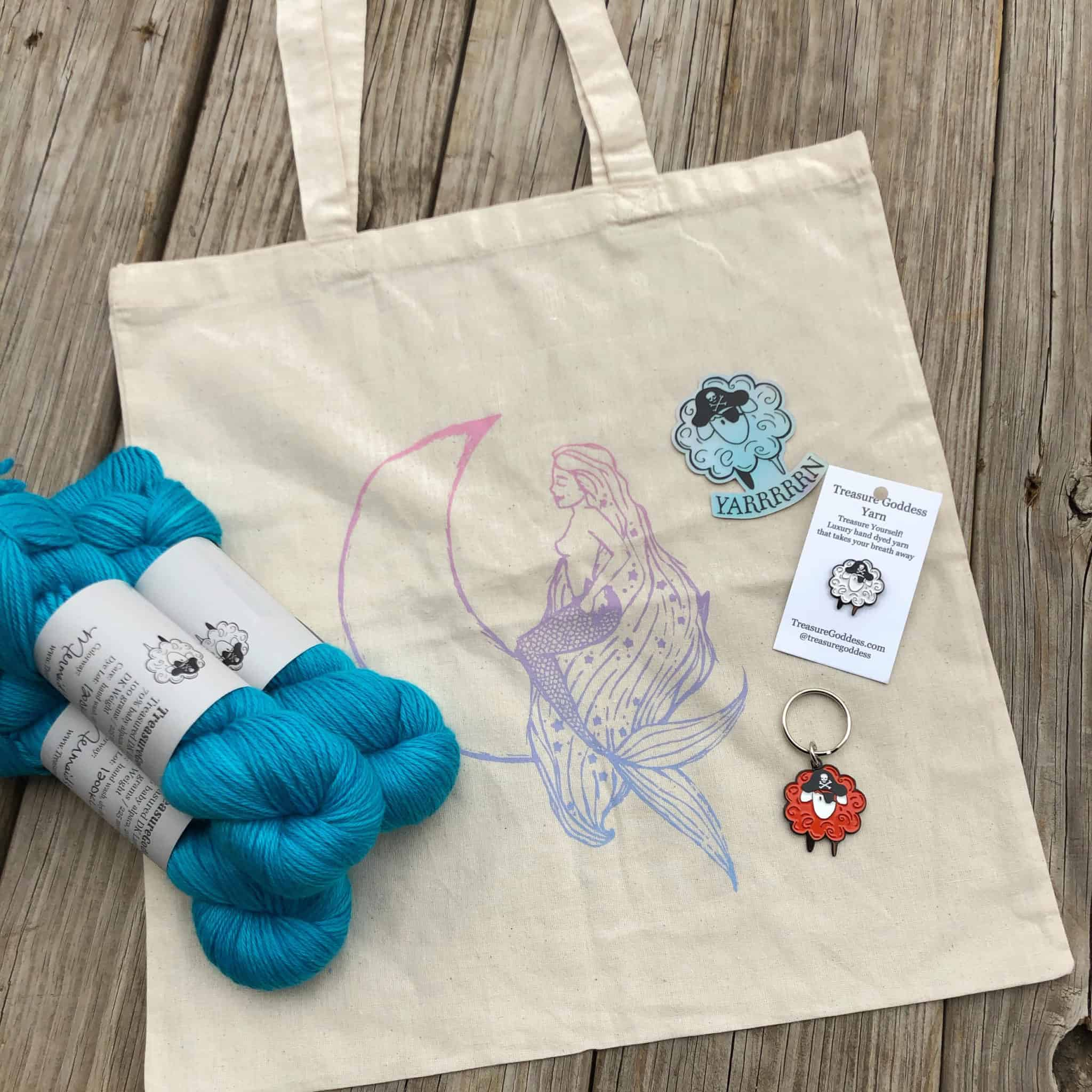 Blue yarn on a natural cotton tote bag with a mermaid.