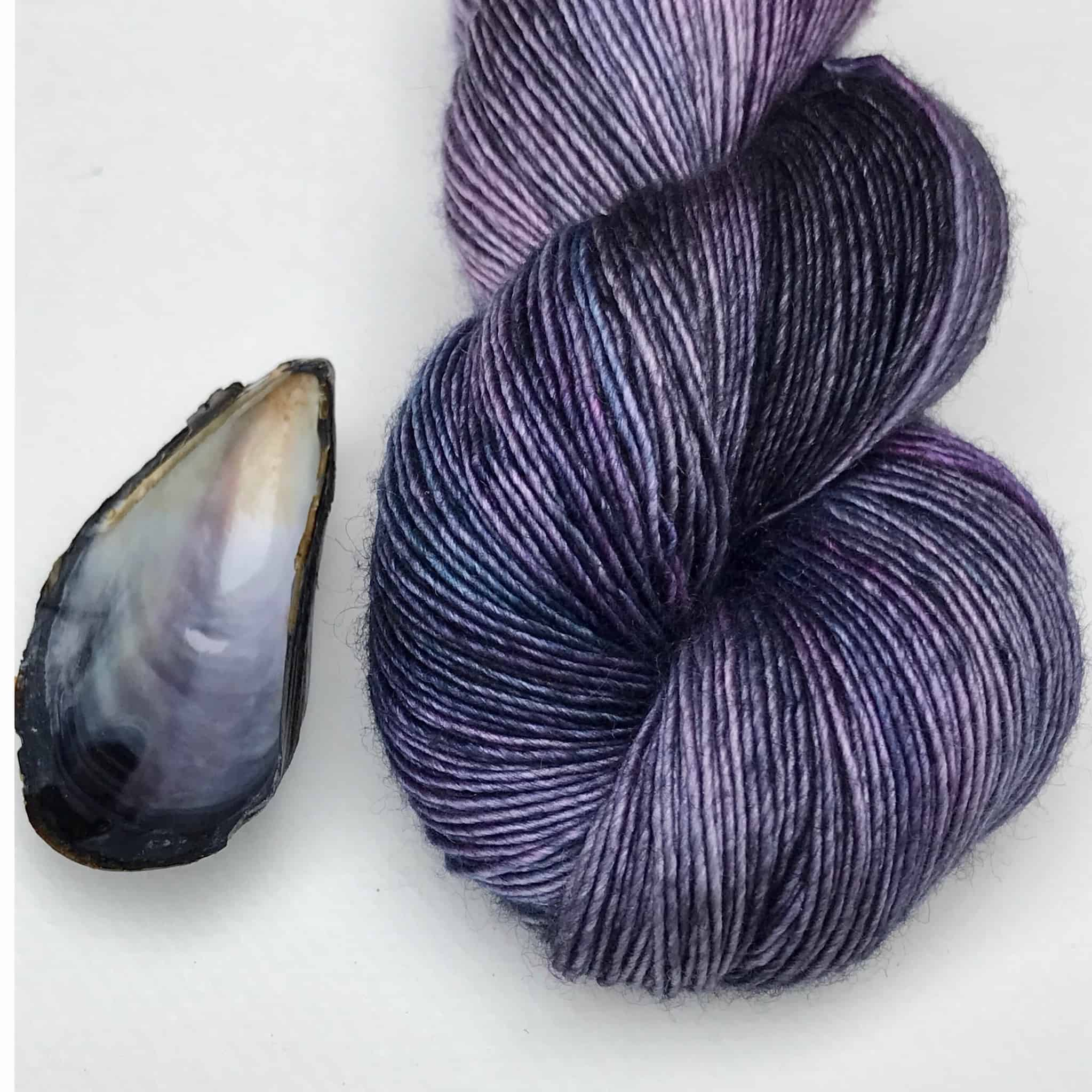 A skein of purple yarn next to a seashell.