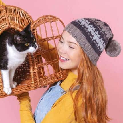 A woman in a gray colorwork hat with a black and white cat.