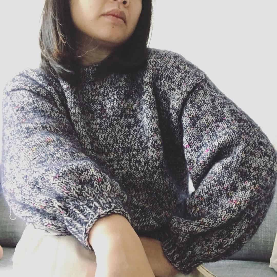 A woman poses in a navy speckled sweater
