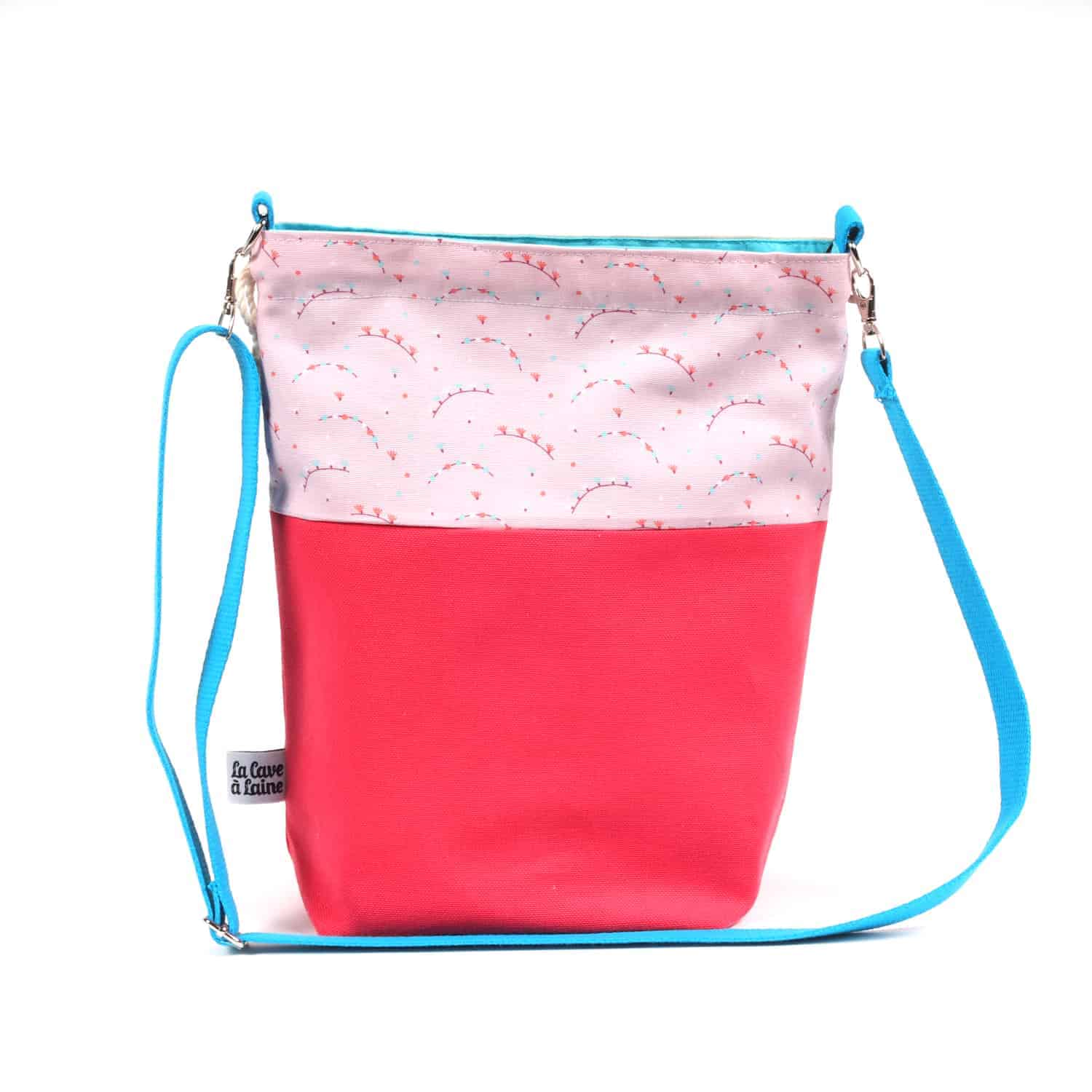 A two-toned pink bag with a blue strap.