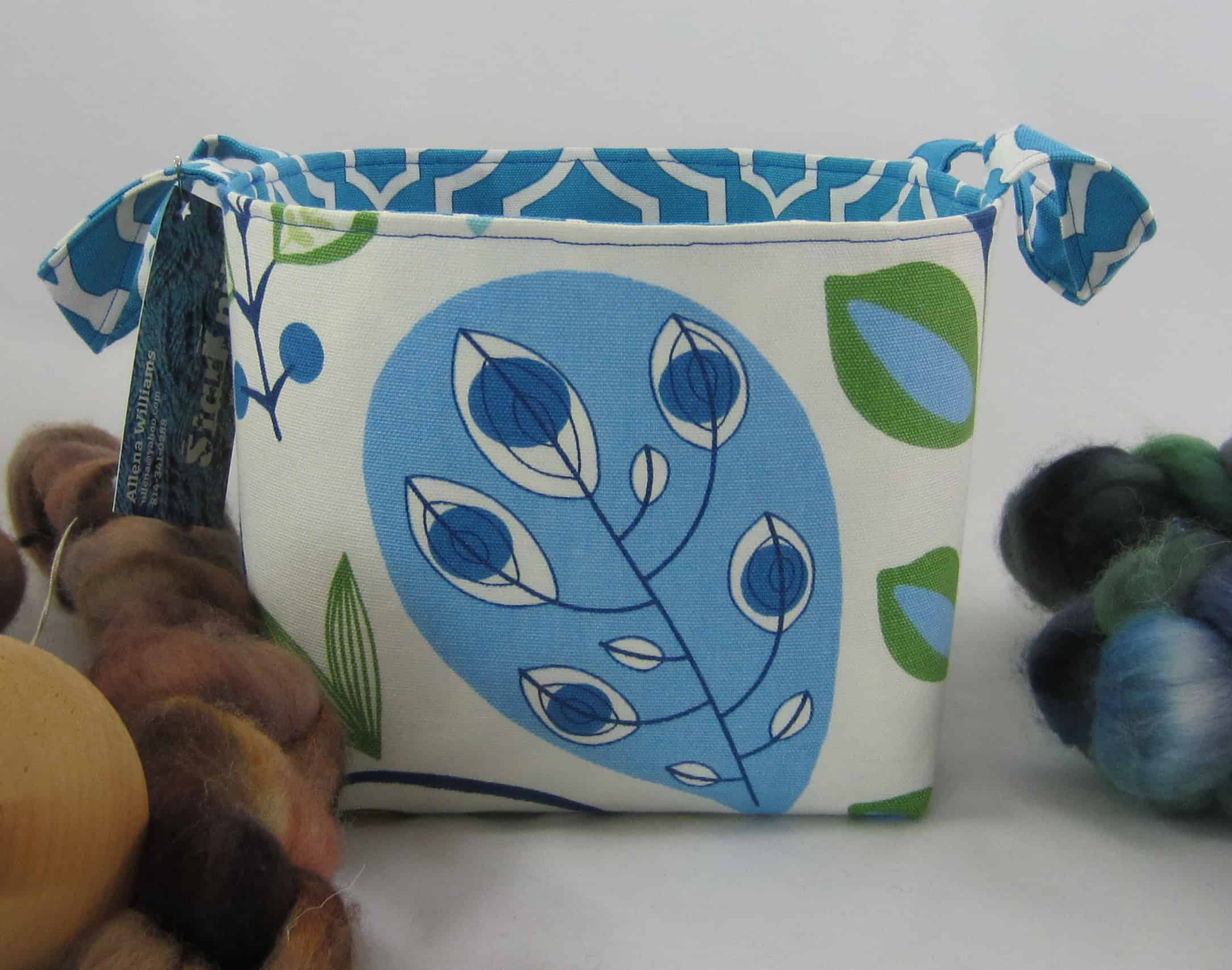 A white bag with a blue and green leaf pattern.