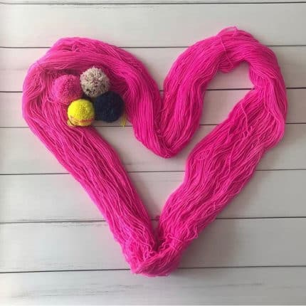 Pink yarn in the shape of a heart.