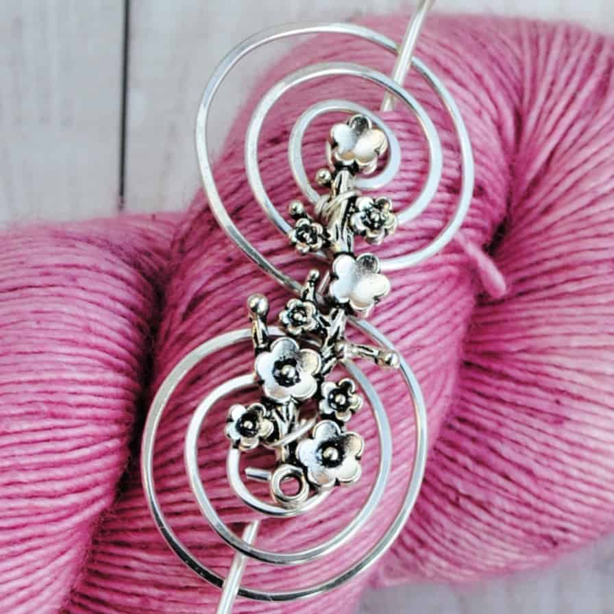 A silver shawl pin on a skein of pink yarn.