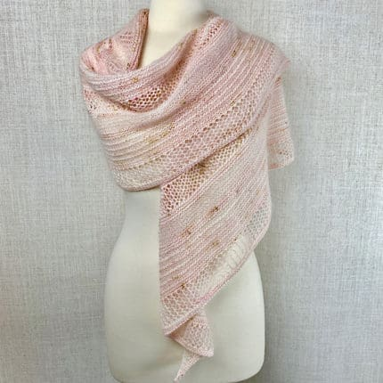 A pale pink lace shawl sits on a dress form.