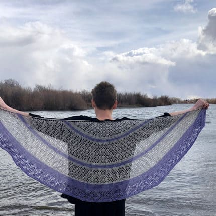 A woman holds a gray and purple lacy shawl.