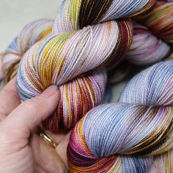 A hand touches a skein of multicolored yarn.