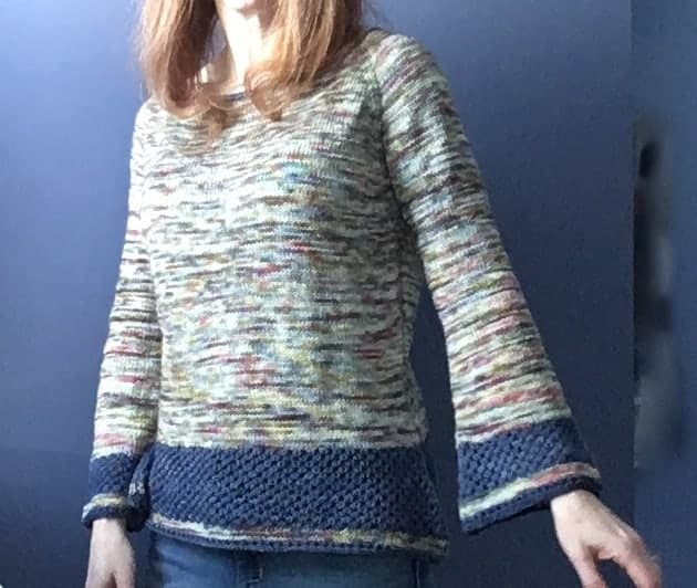 A bell sleeve sweater in mint speckled yarn with a dark blue accents at the hem and sleeves.