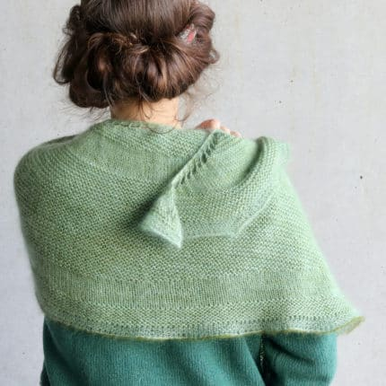 A mint green knit shawl sits on a woman's shoulders.