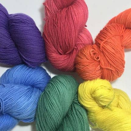 A rainbow of yarn laid out in a circle.