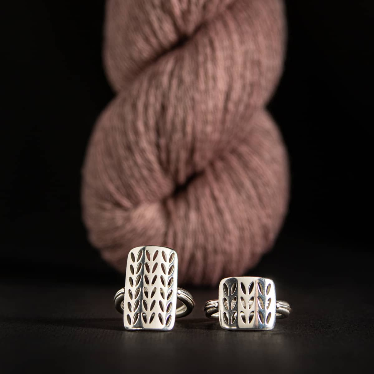 Silver rings sit in front of a skein of pink yarn.