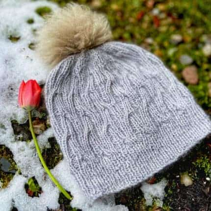 A silver cabled hat with a gold pompom.