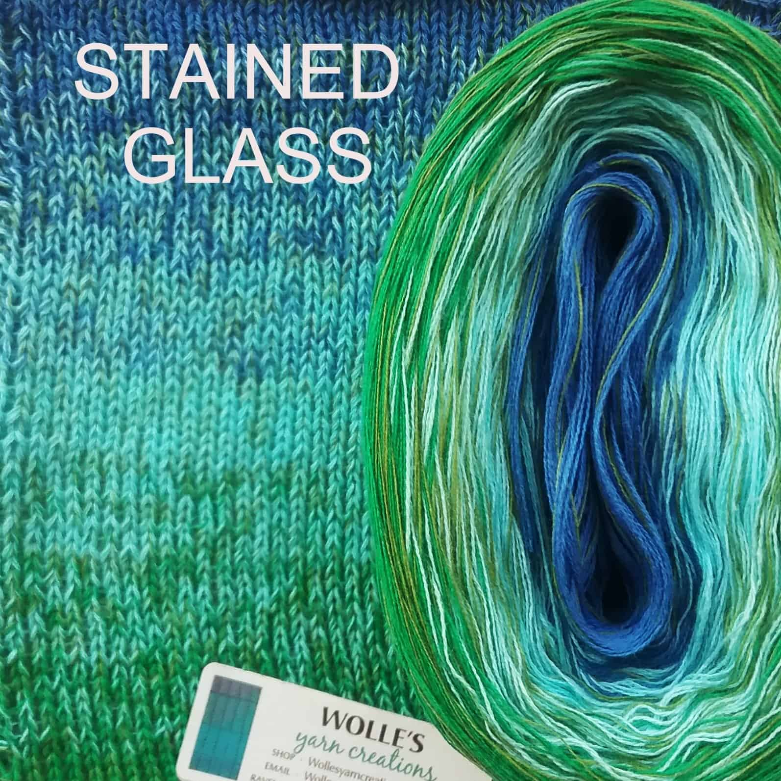 A cake of ombre yarn from blue to great and the words Stained Glass.