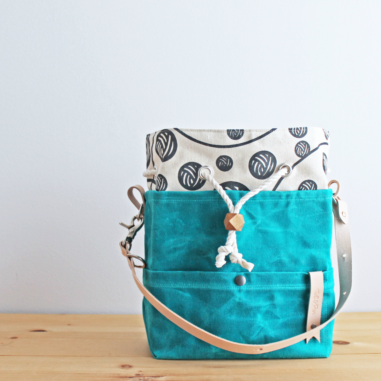 A teal bag with a lining of gray yarn balls and a tan leather strap.