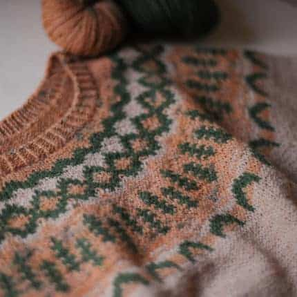 A peach and forest green colorwork yoke sweater.