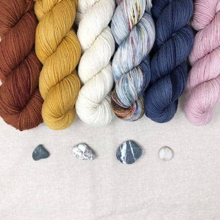 Skeins of red, gold, white, blue and pink yarn above stones.