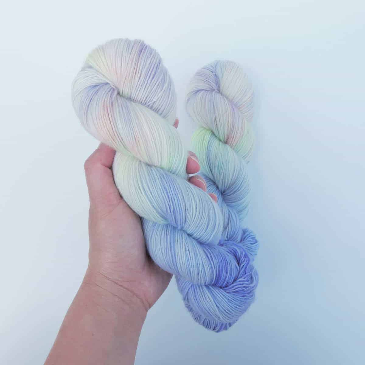 A hand holds neon tie dye yarn.