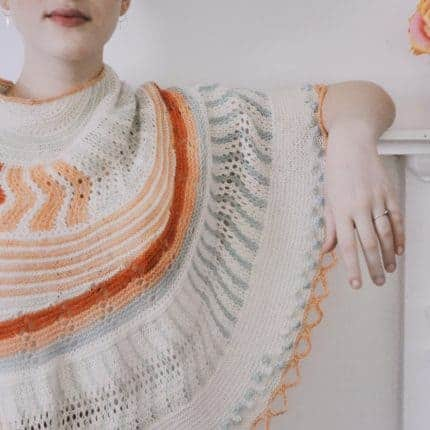 A shawl with geometric patterns in shades of cerulean, coral and cream.