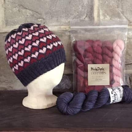 A navy knit hat with pink hearts.