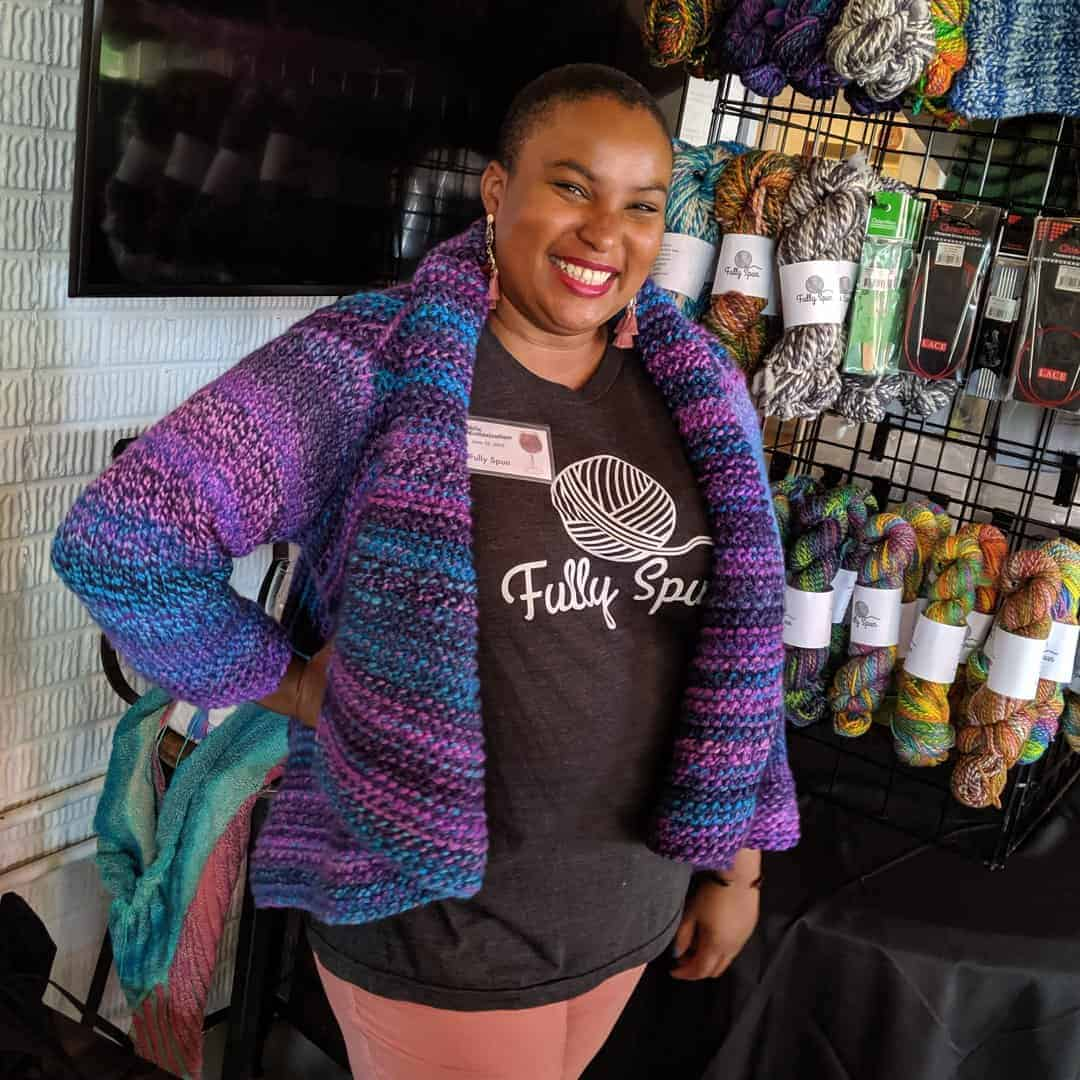 A black woman in a blue and purple cardigan smiles in front of a wall of colorful yarn.