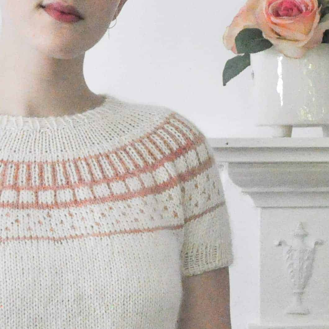 A woman models a white sweater with pale orange colorwork.