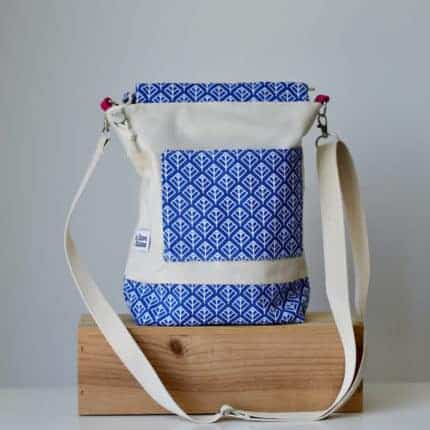A white and blue bucket back with a white strap.