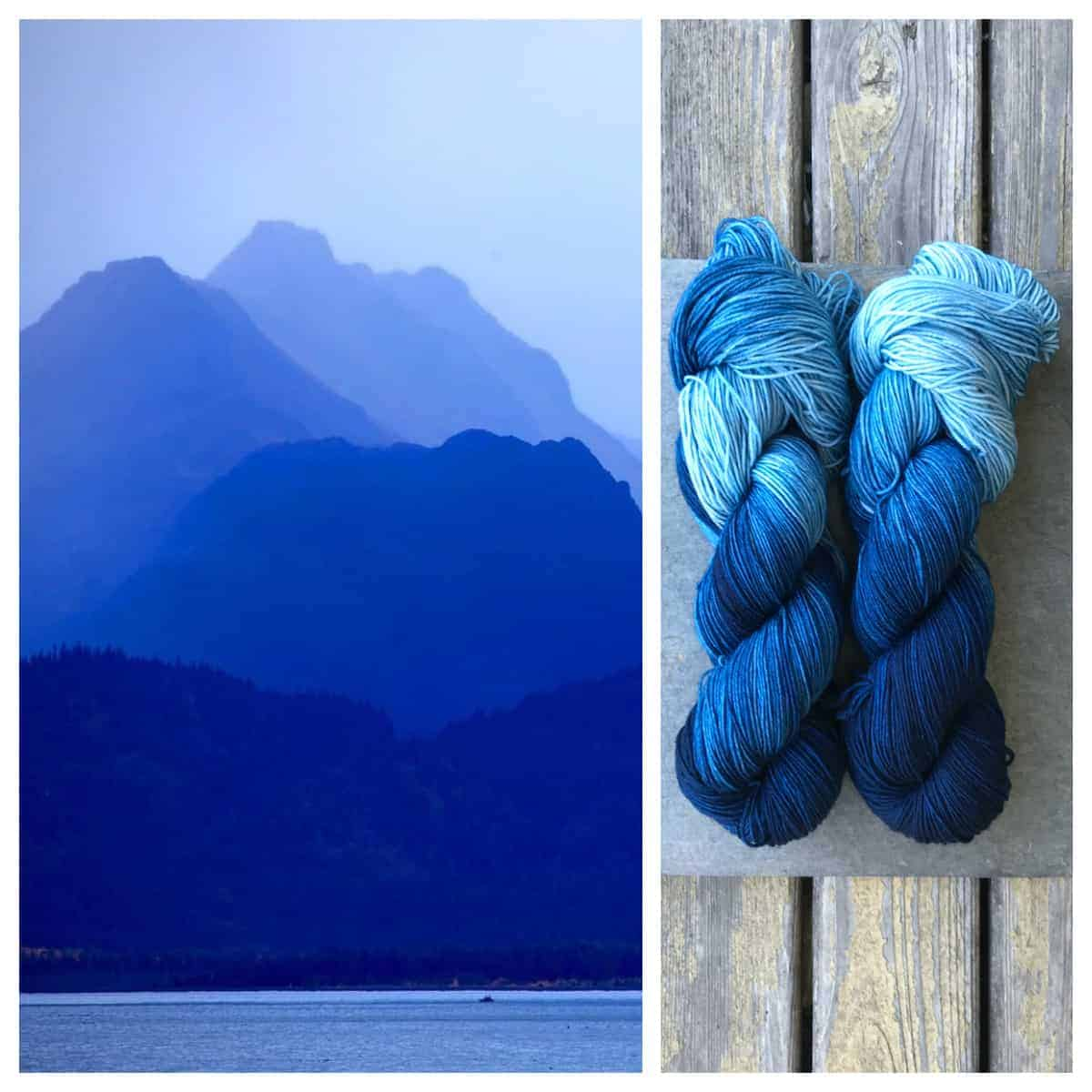 Mountains in shades of blue and two skeins of dark to light blue hand-dyed yarn.