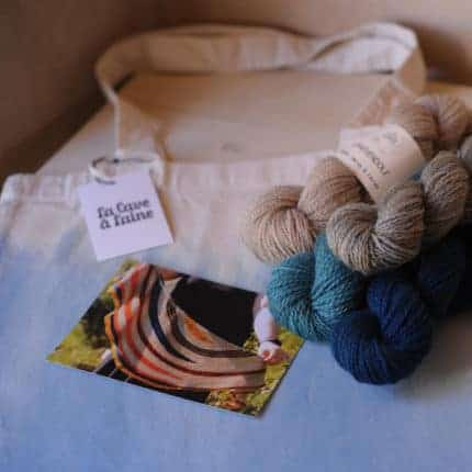 Skeins of blue and silver yarn over a hand-dyed tote bag.