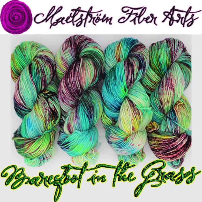Green, aqua and purple speckled yarn with the words Maelstrom Fiber Arts Barefoot in the Grass.