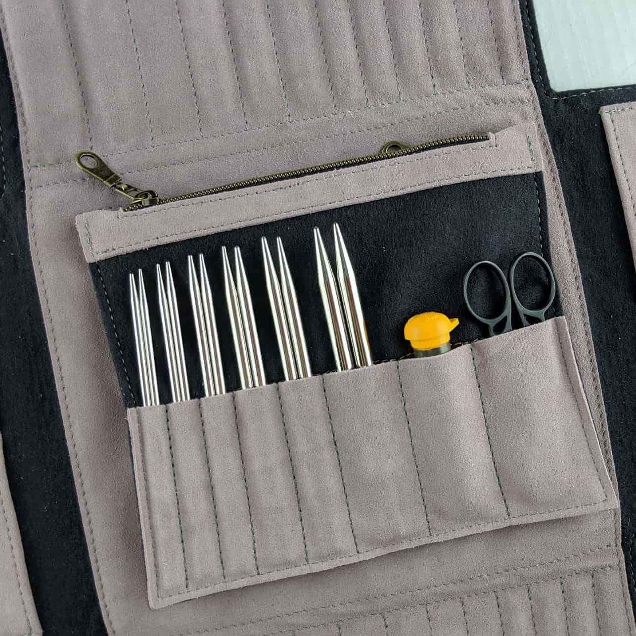 A gray and black case holding metal knitting needle tips.