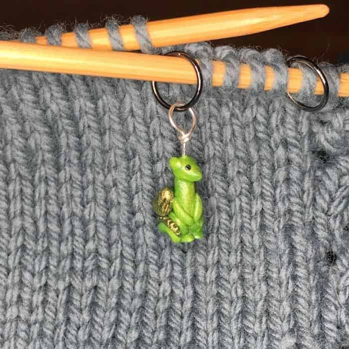 A green dragon stitch marker on wooden knitting needles.