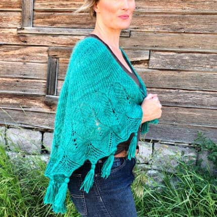 A teal knit shawl with brioche, lace and tassels.