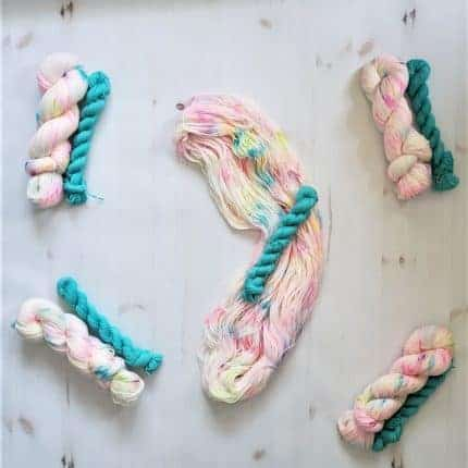 Skeins of pink speckled yarn with teal mini skeins.