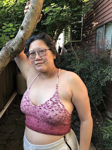 A woman models a pink bralette.