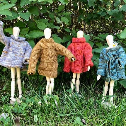 Mini mannequins wearing colorful mini sweaters.
