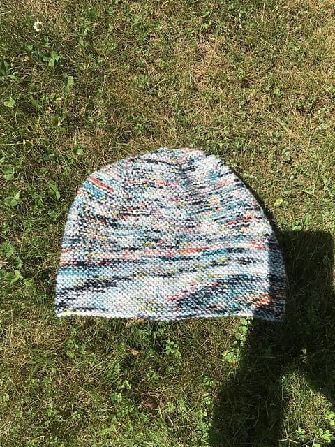 A white, pink, blue and gray speckled hat.