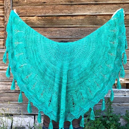 A teal shawl with lace and tassels.