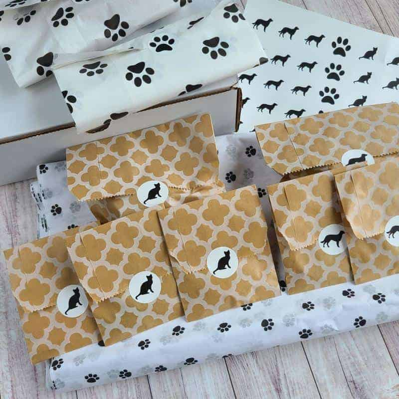Packages with black and white cat stickers and dog paw tissue paper.