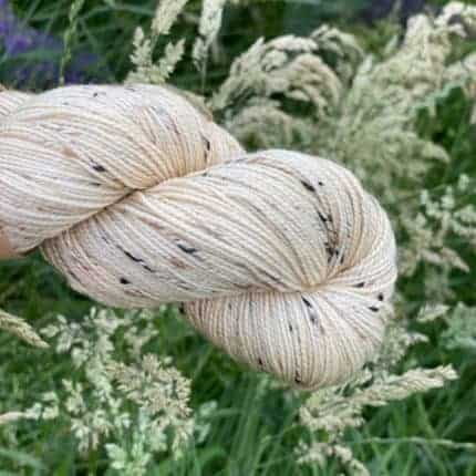 Cream yarn with flecks of purple.