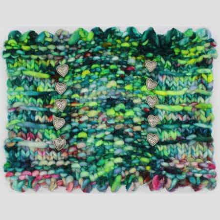 A chunky cowl in green, blue and pink speckled bulky yarn.
