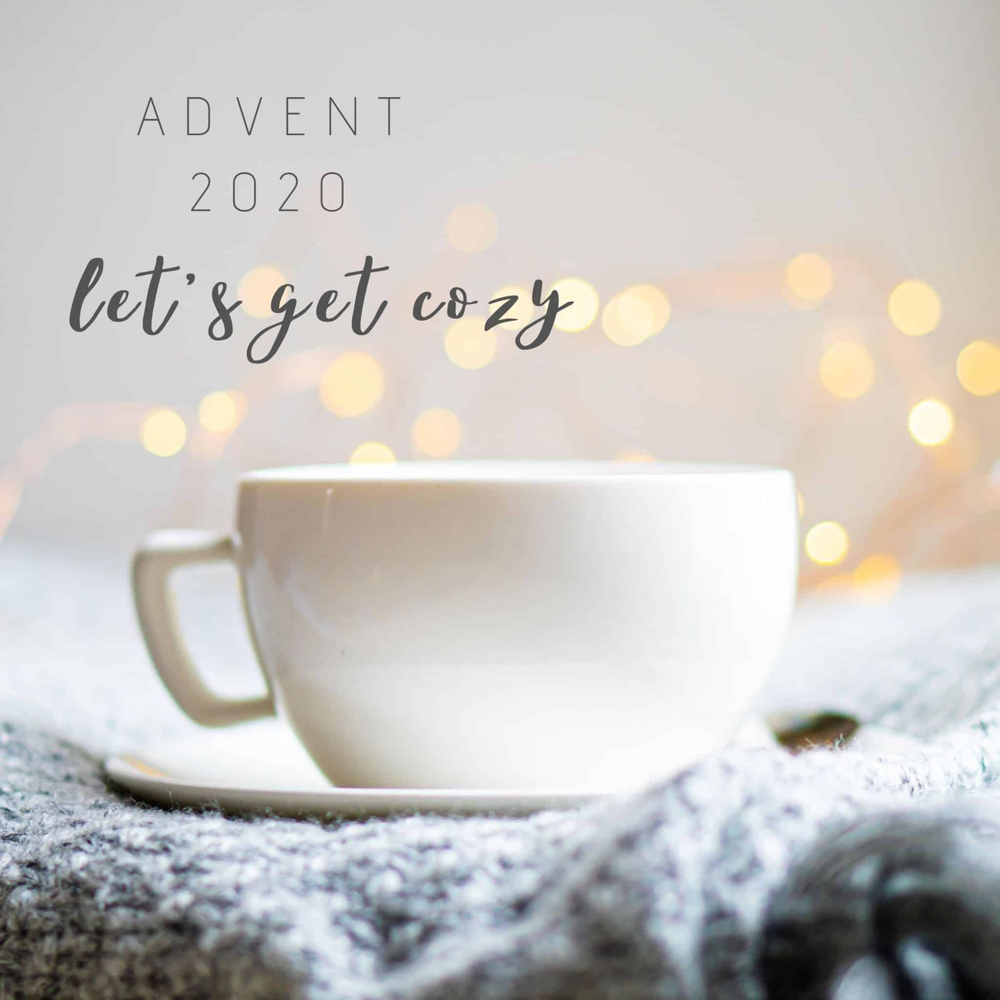 A white teacup sits in front of fairy lights on a handknit with the worlds Advent 2020 let's get cozy.