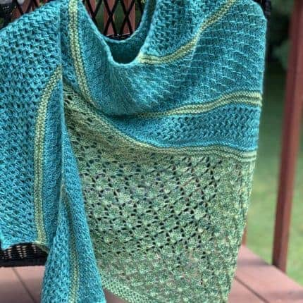 A teal and green lacy and textured shawl.