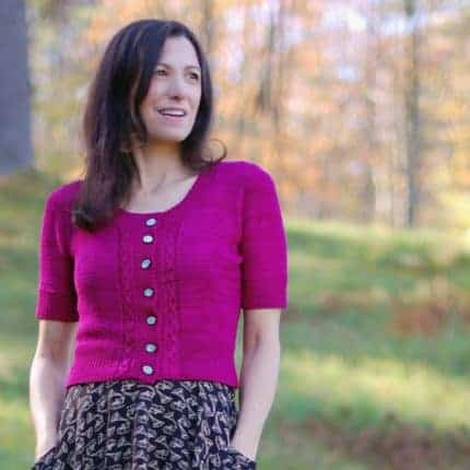 A woman wearing a pink short sleeved cardigan.